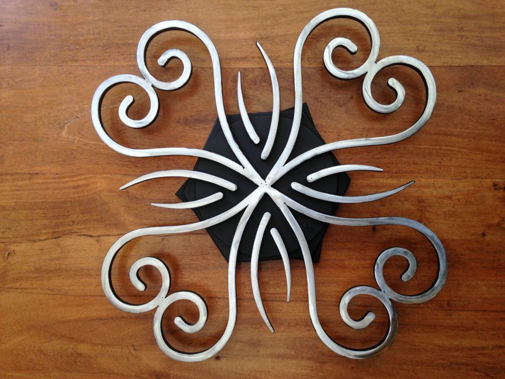 """Dessous de plat """"rotatif"""" en fer forgé Finition : peinture noir mat et acier brut"""