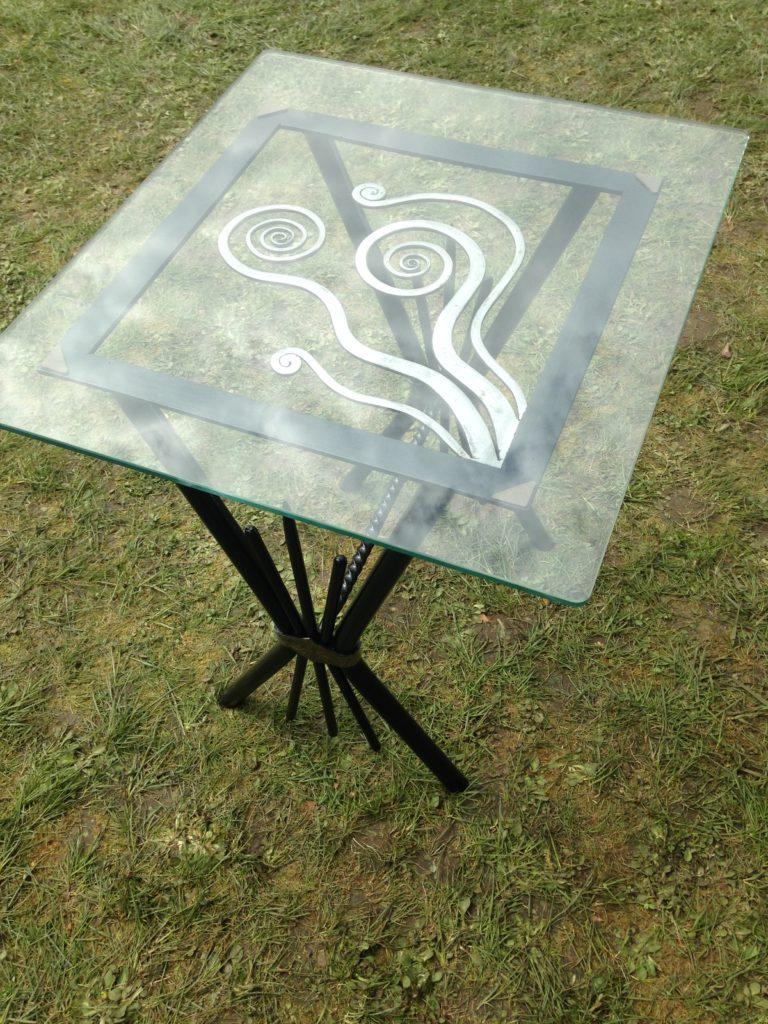 Table basse en fer forgé, décor de fleurs. Finition : peinture noir brillant