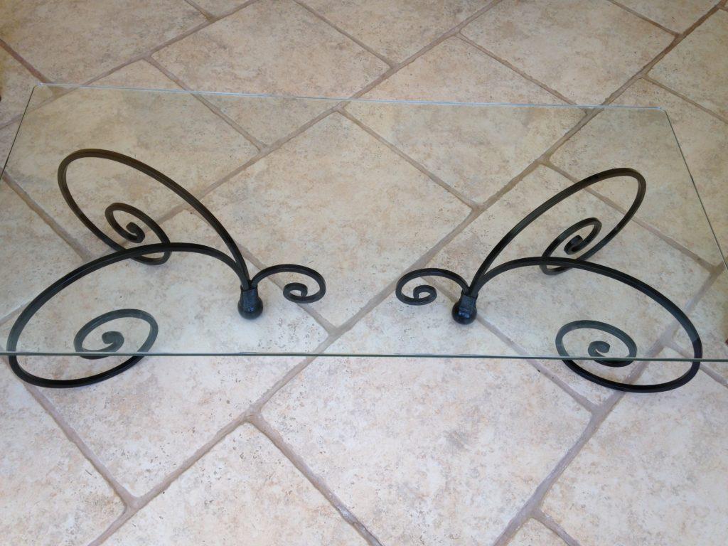 Table basse en fer forgé, pieds volutes dessus verre Finition noir brillant